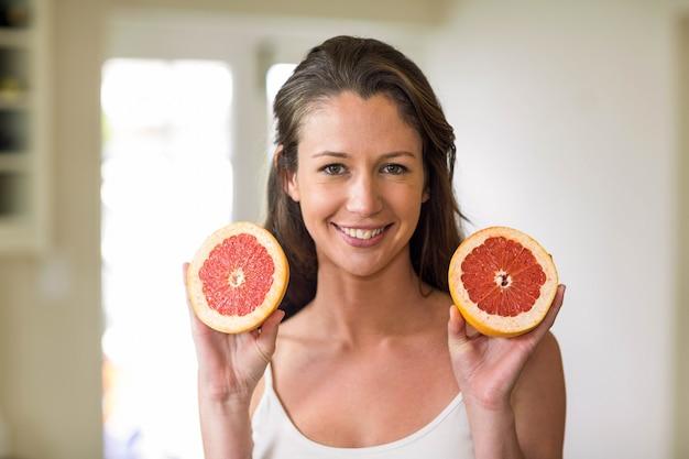 Mujer joven con rodajas de naranja de sangre en la cocina
