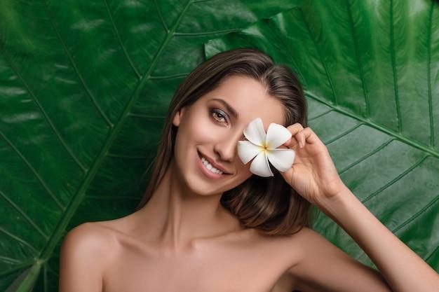 Mujer joven rodeada de hojas tropicales