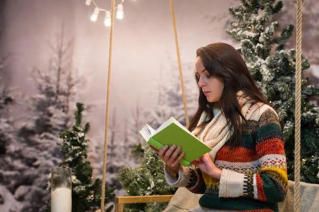 Mujer joven romántica leyendo un libro mientras está sentada en un columpio con una manta bajo las linternas en un parque cubierto de nieve con abetos, vistiendo suéter de lana y bufanda de punto