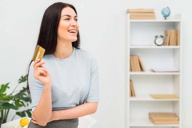 Mujer joven en la ropa azul que se coloca con la tarjeta de crédito en oficina