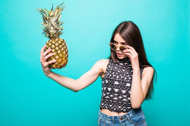 Mujer joven en ropa casual con gafas de sol withp con piña en manos aisladas