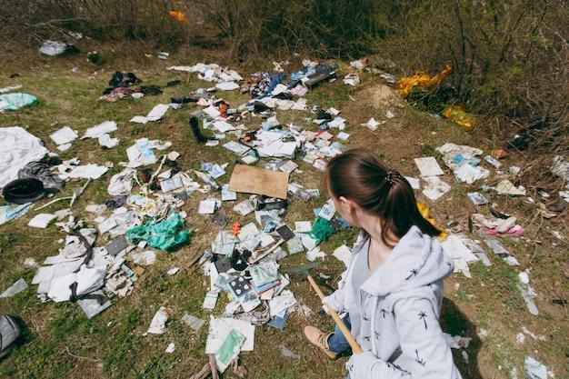 Mujer joven en ropa casual y guantes de látex para limpiar con rastrillo para la recolección de basura en el parque lleno de basura