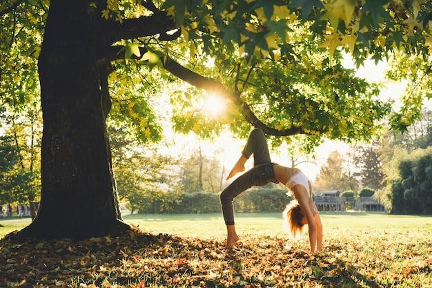 Mujer joven en ropa casual haciendo pose de yoga en el parque. chica practica yoga al aire libre. mujer con cuerpo delgado, fuerte y flexible. estilos de vida saludables.