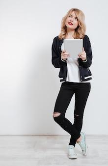 Mujer joven en ropa casual pensando y sosteniendo tablet pc