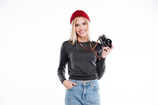 Mujer joven en ropa casual de pie y sosteniendo la cámara retro