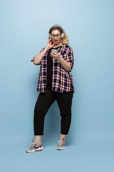 Mujer joven en ropa casual con smartphone y auriculares en la pared azul. carácter positivo del cuerpo, feminismo, amarse a sí misma, concepto de belleza. plus tamaño hermosa empresaria. inclusión, diversidad.