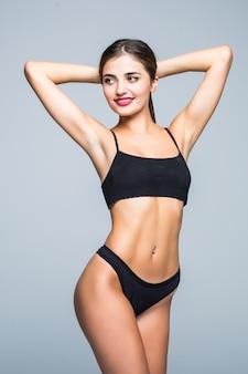 Mujer joven con ropa de cuerpo perfecto en ropa interior negra en la pared blanca