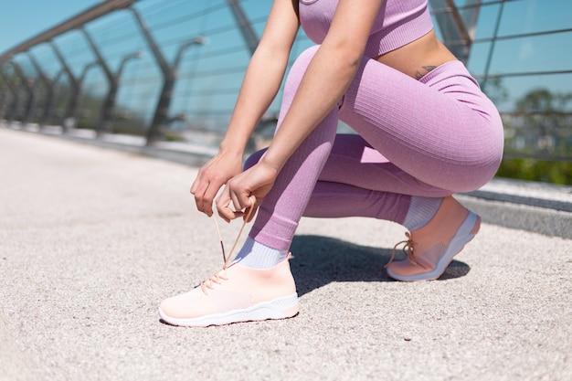 Mujer joven en ropa deportiva adecuada en el puente en la calurosa mañana soleada ata los cordones de los zapatos