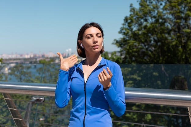 Mujer joven en ropa deportiva azul en el puente en la calurosa mañana soleada con auriculares inalámbricos descansando ola con las manos, cansada después de hacer ejercicio trotar