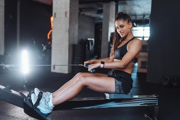Mujer joven en ropa deportiva en el gimnasio, entrenando y tirando de pesas en la máquina de fila de cable sentado.