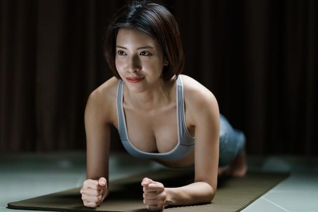 Mujer joven en ropa deportiva gris ejercicio en casa, haciendo una tabla