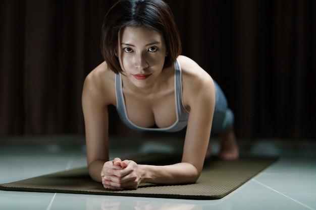 Mujer joven en ropa deportiva gris ejercicio en casa