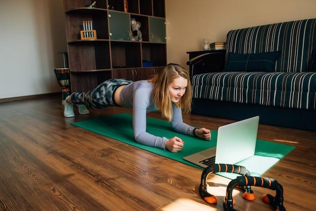 Mujer joven en ropa deportiva haciendo tablón sobre estera en casa