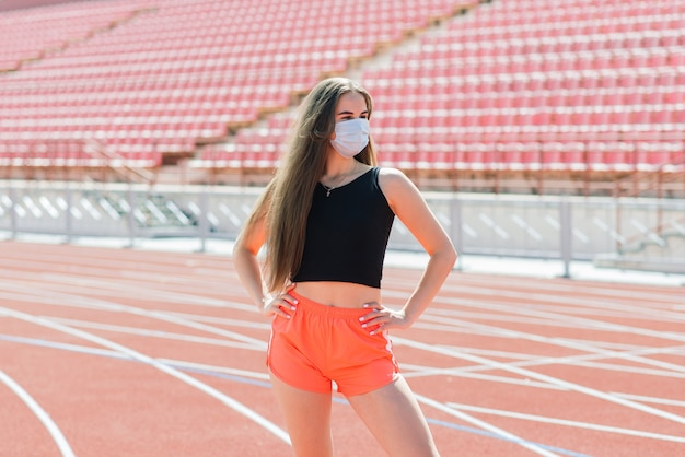 Mujer joven en ropa deportiva y máscara protectora para coronavirus en pista roja y campo de voleibol durante el entrenamiento al aire libre en el estadio
