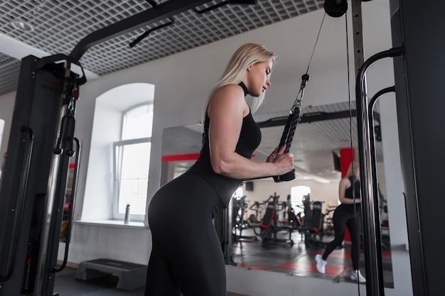 Mujer joven en ropa deportiva negra está haciendo ejercicios de fuerza para las manos en el gimnasio moderno.