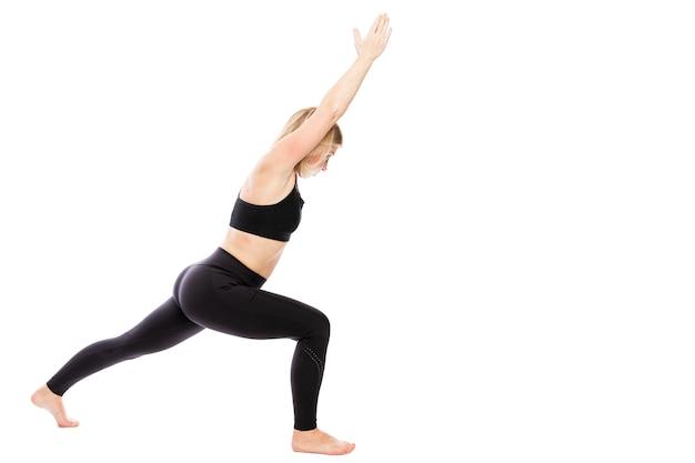 Mujer joven en ropa deportiva negra en pose de yoga. estilo de vida saludable. aislado sobre fondo blanco. espacio para texto.