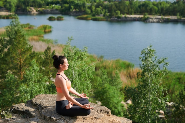 Mujer joven en ropa deportiva sentada en posición de loto y haciendo ejercicio de respiración al aire libre