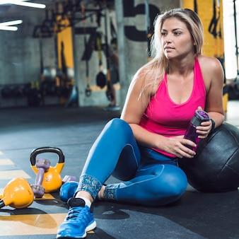 Mujer joven en ropa deportiva sentado en el piso