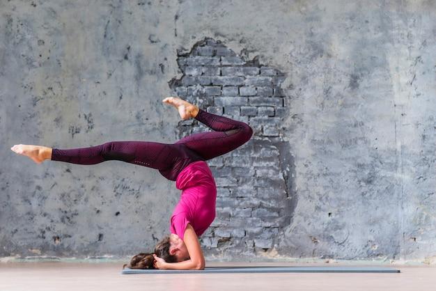 Mujer joven con ropa deportiva trabajando contra la pared gris