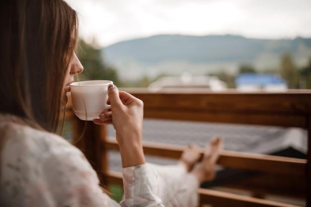 Mujer joven en ropa de dormir elegante disfrutar bebiendo café o té al aire libre en el balcón por la mañana