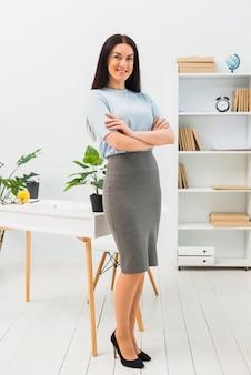 Mujer joven en ropa elegante de pie con los brazos cruzados