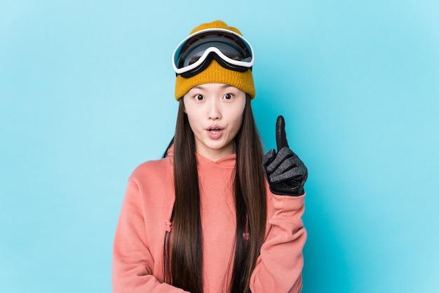 Mujer joven con ropa de esquí que tiene una gran idea