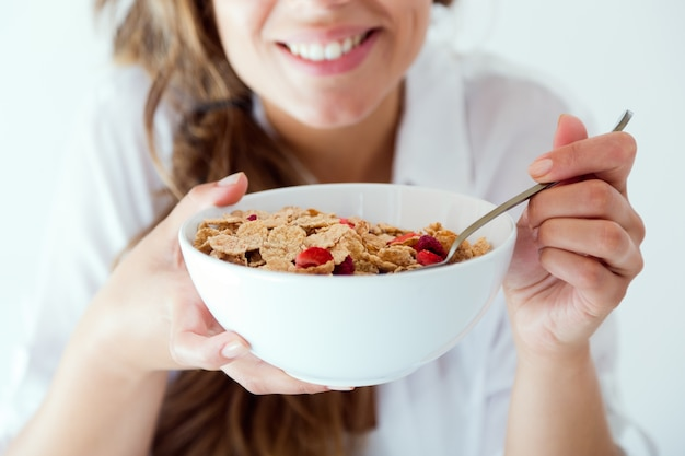 Mujer joven en ropa interior comiendo cereales. aislado en blanco