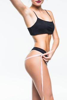 Mujer joven en ropa interior negra que mide su cintura con cinta métrica.
