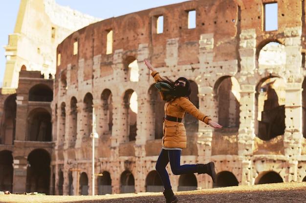 Mujer joven en ropa de invierno divirtiéndose en el coliseo de roma