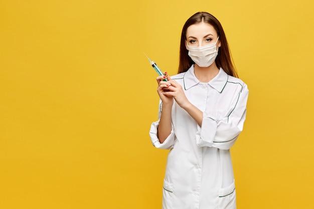 Mujer joven en ropa médica y máscara protectora posando con una jeringa