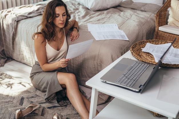 Una mujer joven en ropa de negocios se sienta en el piso de la casa y lee un documento.