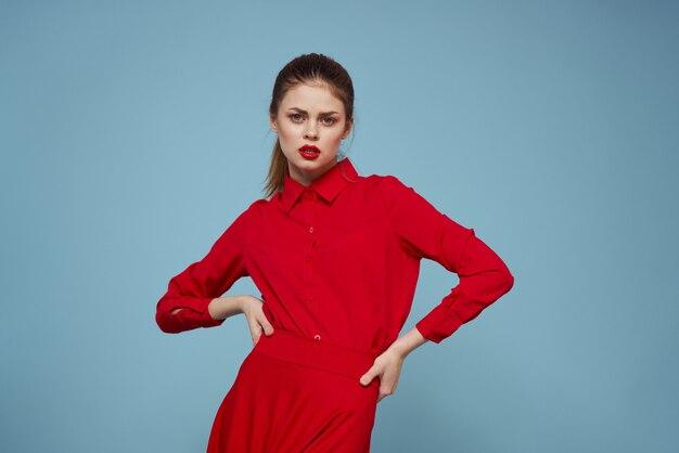 Mujer joven en ropa roja en un espacio azul claro diferentes emociones, moda elegante posando