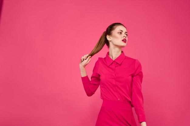 Mujer joven en ropa rosa en un espacio rosa, estilo muñeca divertida