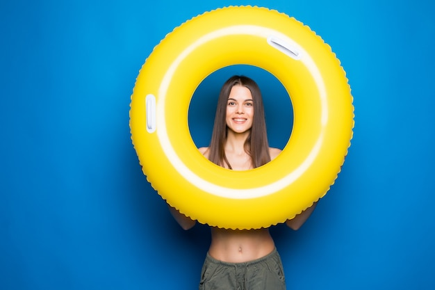 Mujer joven en ropa de verano con anillo inflable aislado sobre pared azul.