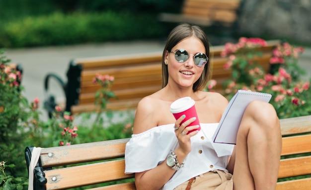 Mujer joven en ropa de verano y gafas de sol sosteniendo una taza de café en sus manos y escribiendo en un cuaderno mientras está sentado en un banco en el parque