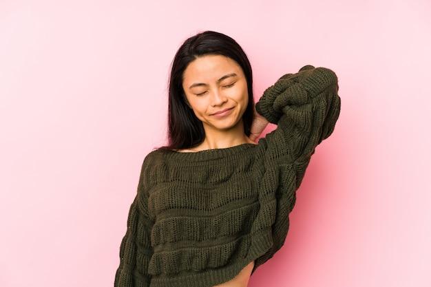 Mujer joven en un rosa que sufre dolor de cuello debido al estilo de vida sedentario.