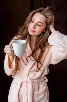 Mujer joven en rosa tierna bata de baño beber té y sonriendo.