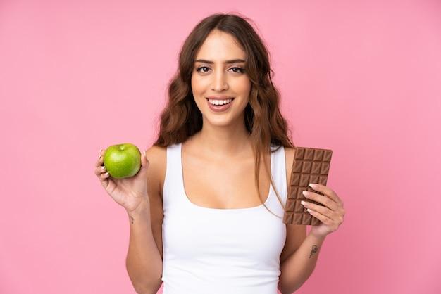 Mujer joven rosa tomando una tableta de chocolate en una mano y una manzana en la otra