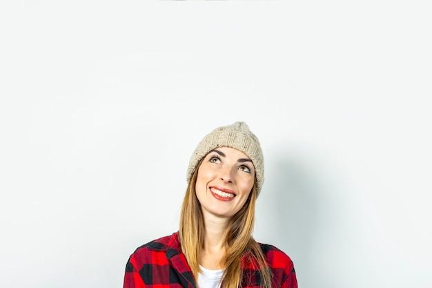 Mujer joven con rostro pensativo sueña con algo en un sombrero, una camisa roja