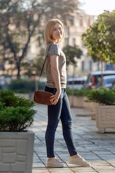 Mujer joven rubia caminando y posando en la calle soleada. mujer caminando en la ciudad al atardecer solo. concepto de estilo de vida relax recreación fin de semana