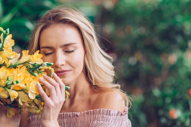 Mujer joven rubia cerrando los ojos tocando las flores de fresia