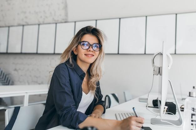 Mujer joven rubia complacida posando en su lugar de trabajo y sosteniendo el lápiz