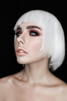 Mujer joven rubia con maquillaje de moda aislada sobre fondo negro