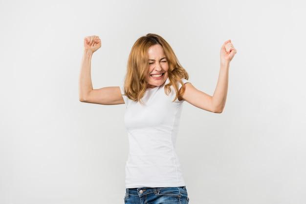Mujer joven rubia emocionada que aprieta su puño contra el contexto blanco