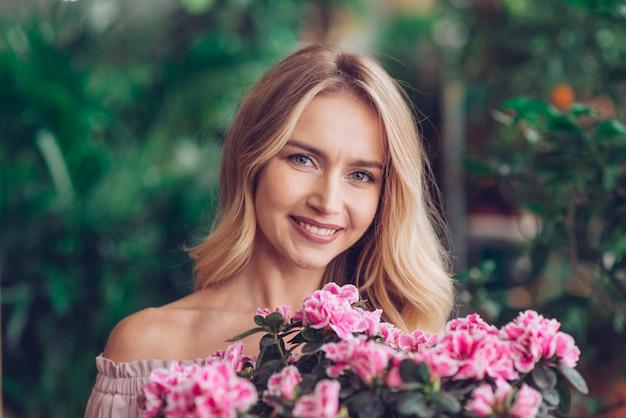 Mujer joven rubia feliz que se coloca detrás de las flores rosadas con el fondo borroso