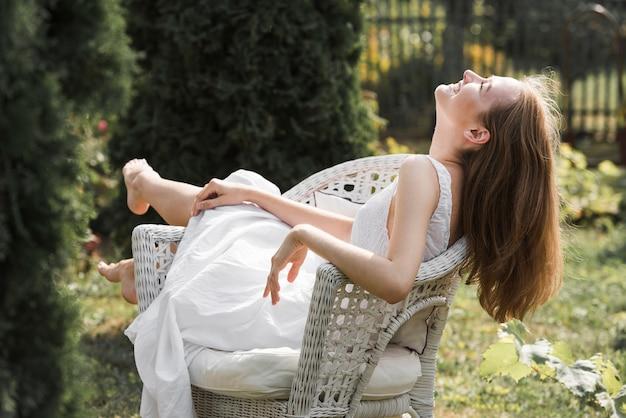 Mujer joven rubia feliz que se relaja en la silla blanca en el jardín