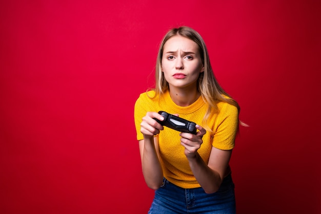 Mujer joven rubia gamer con gamepad jugando videojuegos aislados sobre pared roja