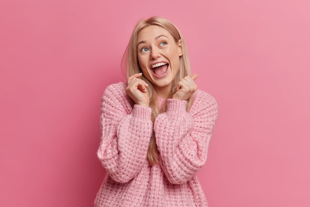 Mujer joven rubia llena de alegría tiene expresión de cara feliz mira arriba mantiene la boca abierta vestida con ropa casual