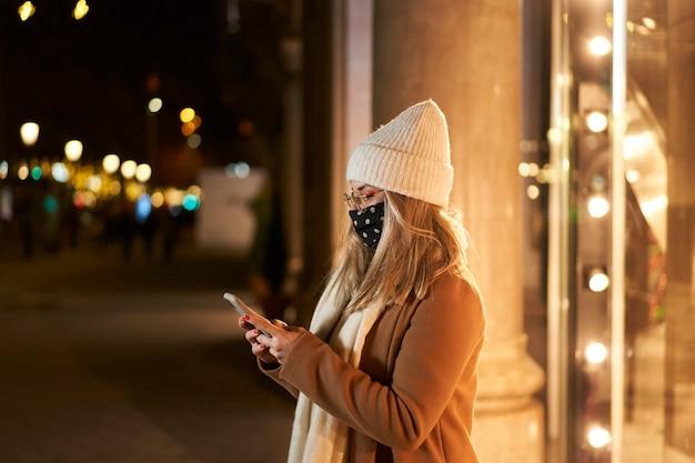 Mujer joven rubia con una máscara delante de un escaparate escribiendo un mensaje, en una ciudad de noche, con luces de fondo. ambiente invernal.