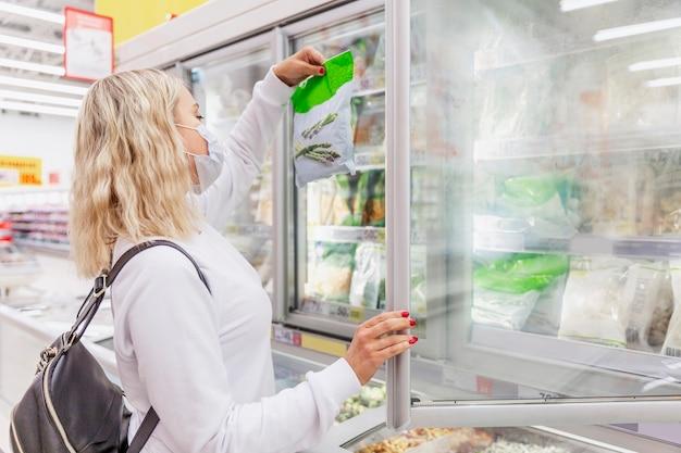 Mujer joven rubia con una máscara médica en el departamento de alimentos congelados. salud y nutrición adecuada durante una pandemia.